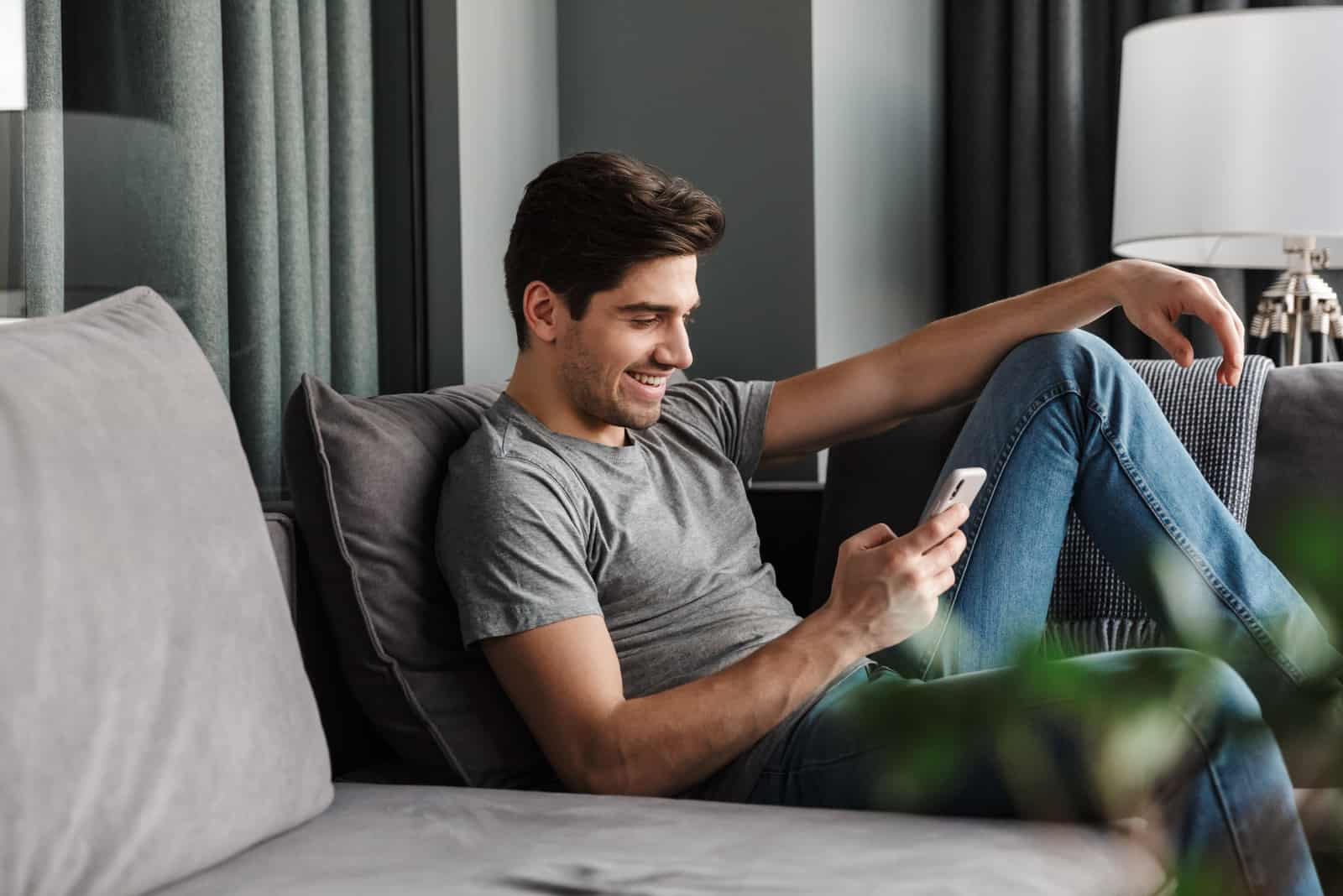 un homme souriant est assis sur le canapé et tape au téléphone
