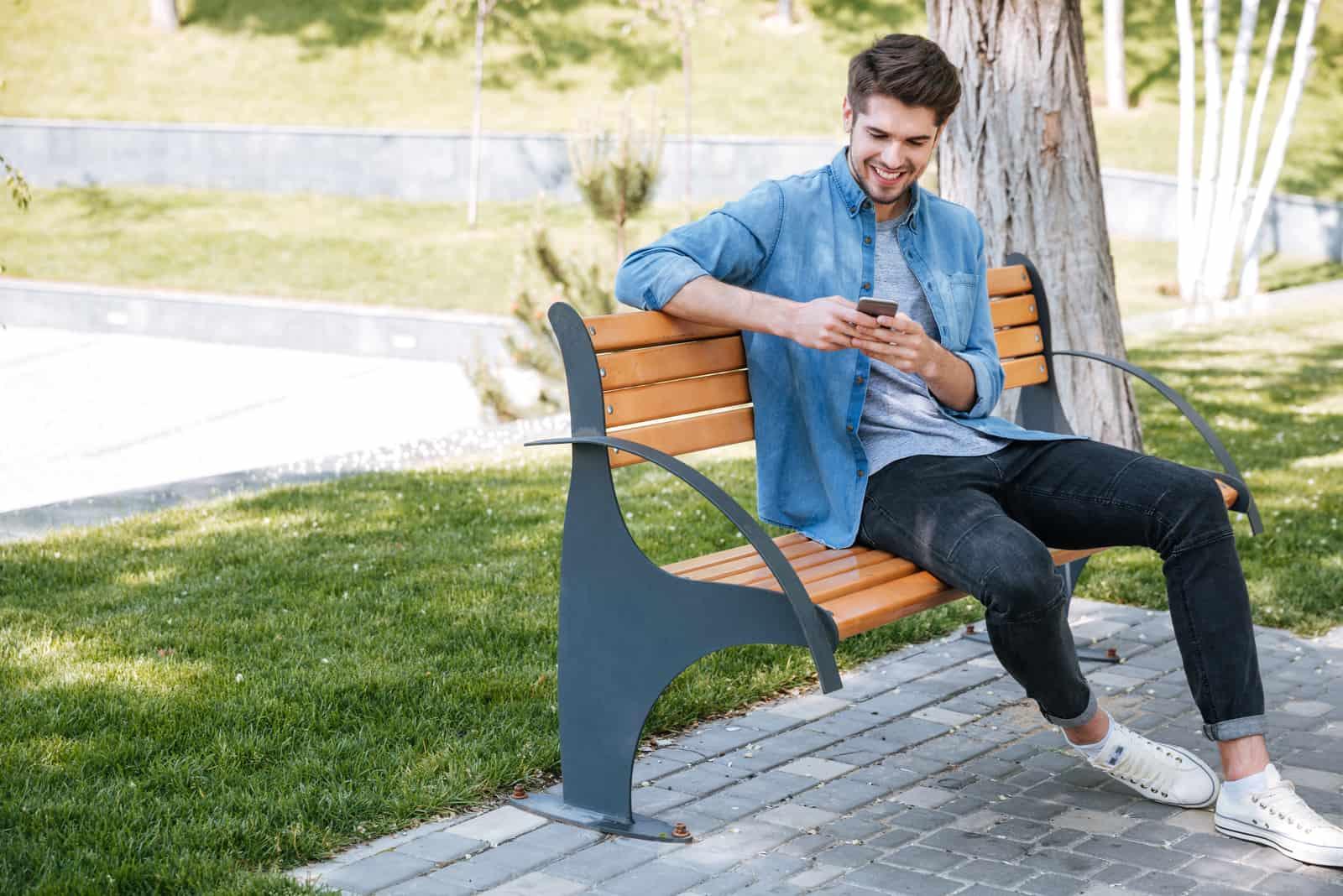 un homme souriant est assis sur un banc de parc et des touches au téléphone