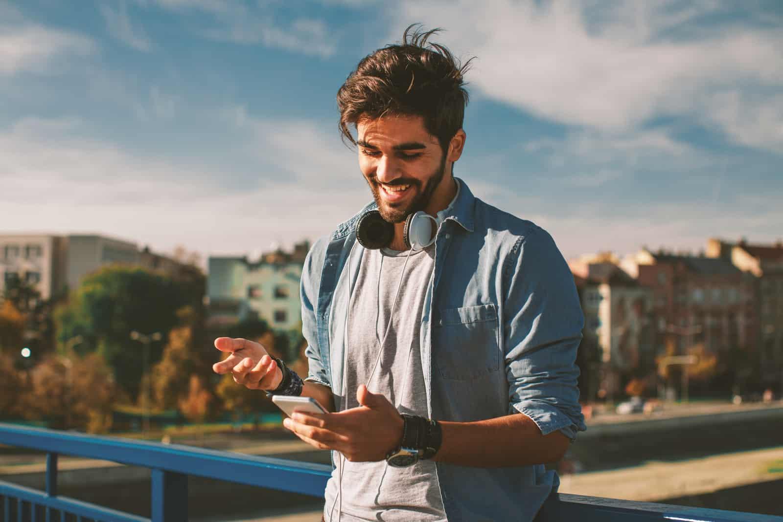 un homme souriant se lève et touche au téléphone