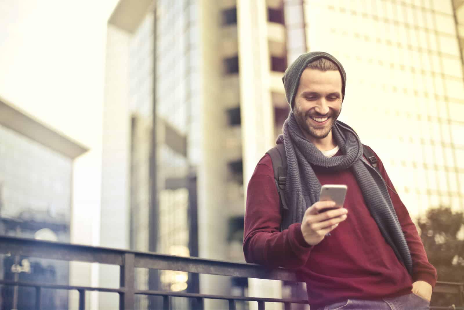 un homme souriant se tient appuyé contre une clôture et pousse un téléphone