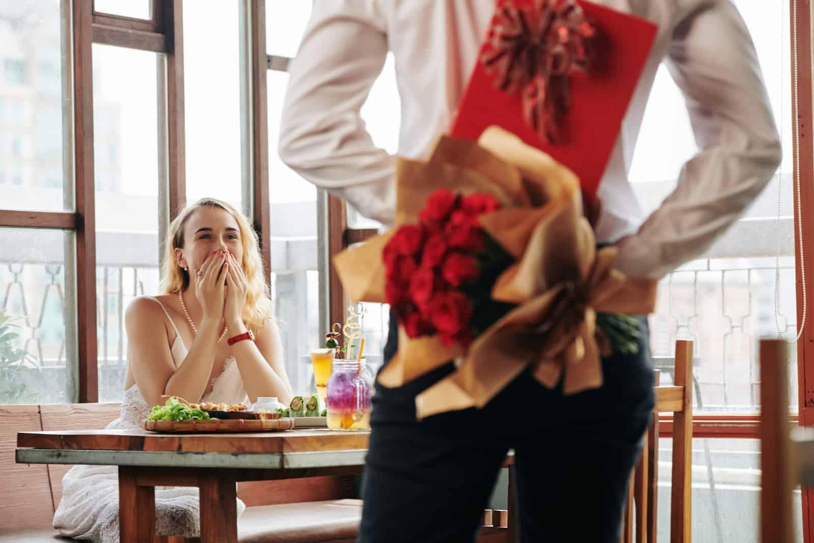 un homme veut surprendre une femme avec un bouquet de roses