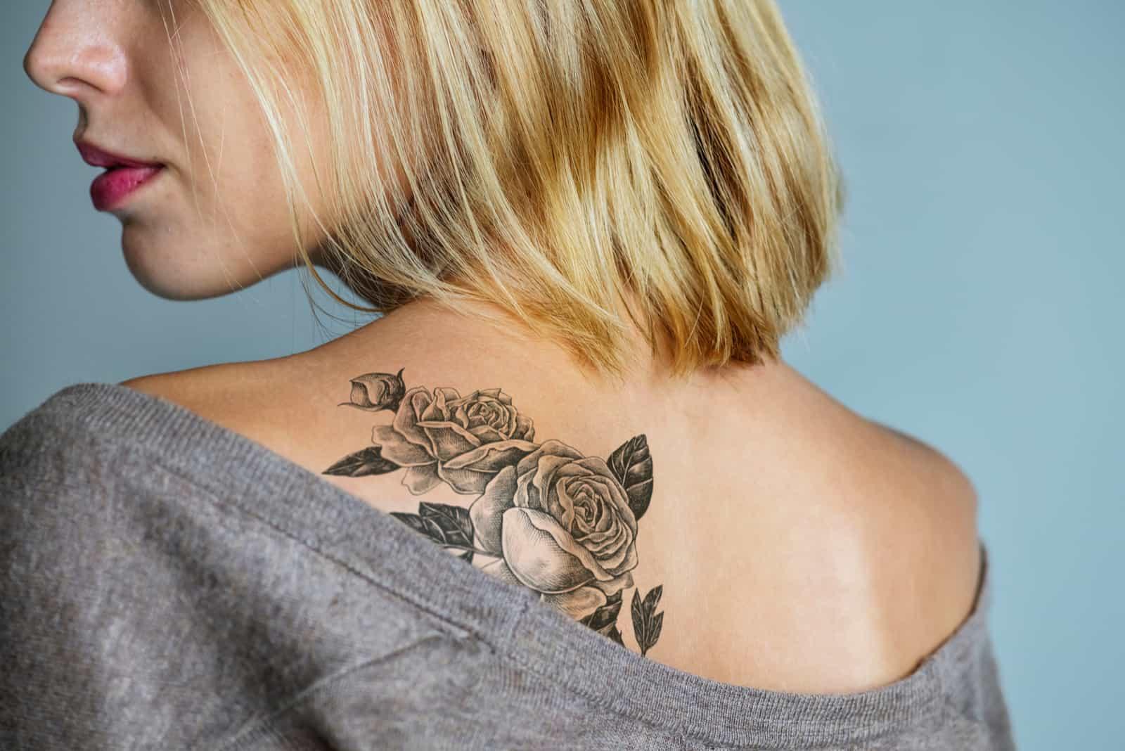 un tatouage de rose sur l'épaule d'une femme