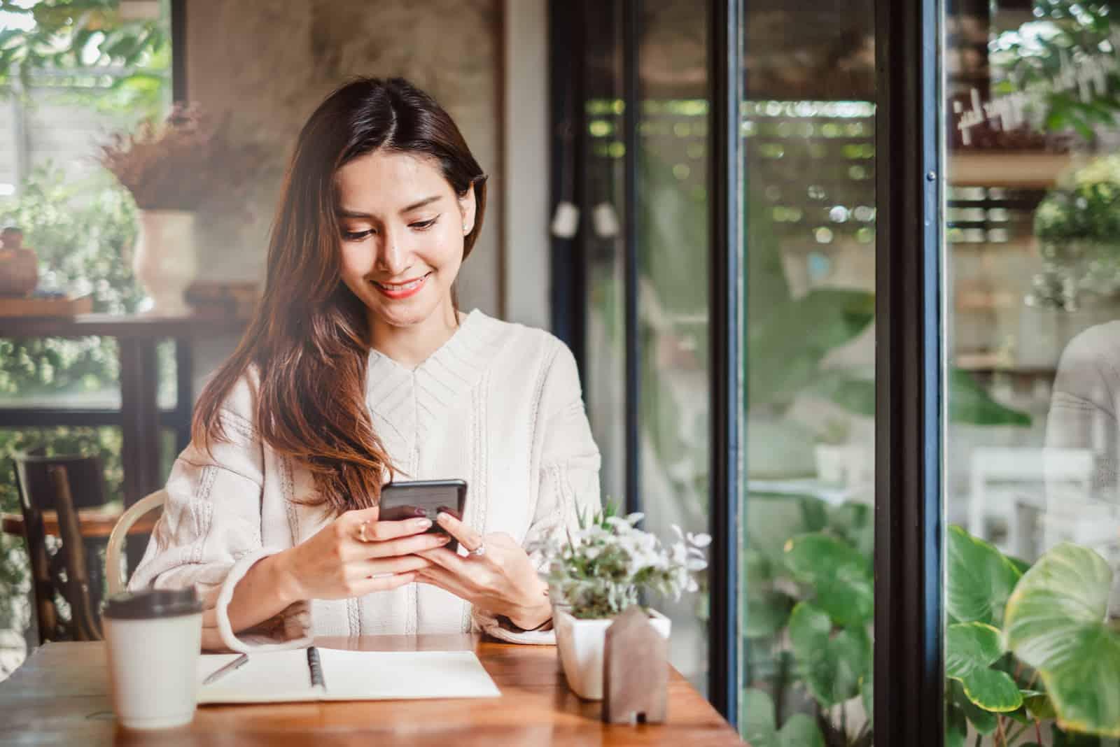 une belle femme aux cheveux bruns est assise à une table et des touches au téléphone