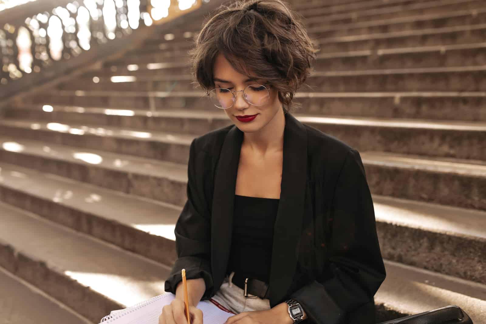 une belle femme est assise dans les escaliers et écrit