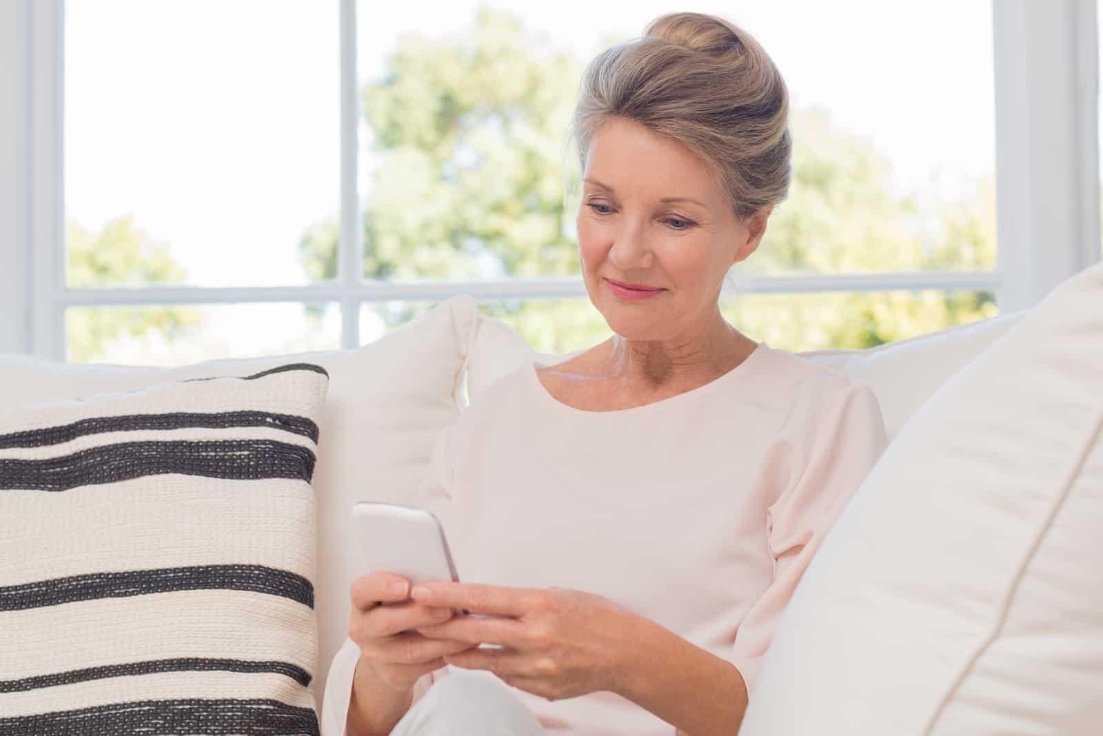 une belle femme est assise sur le canapé et un bouton au téléphone