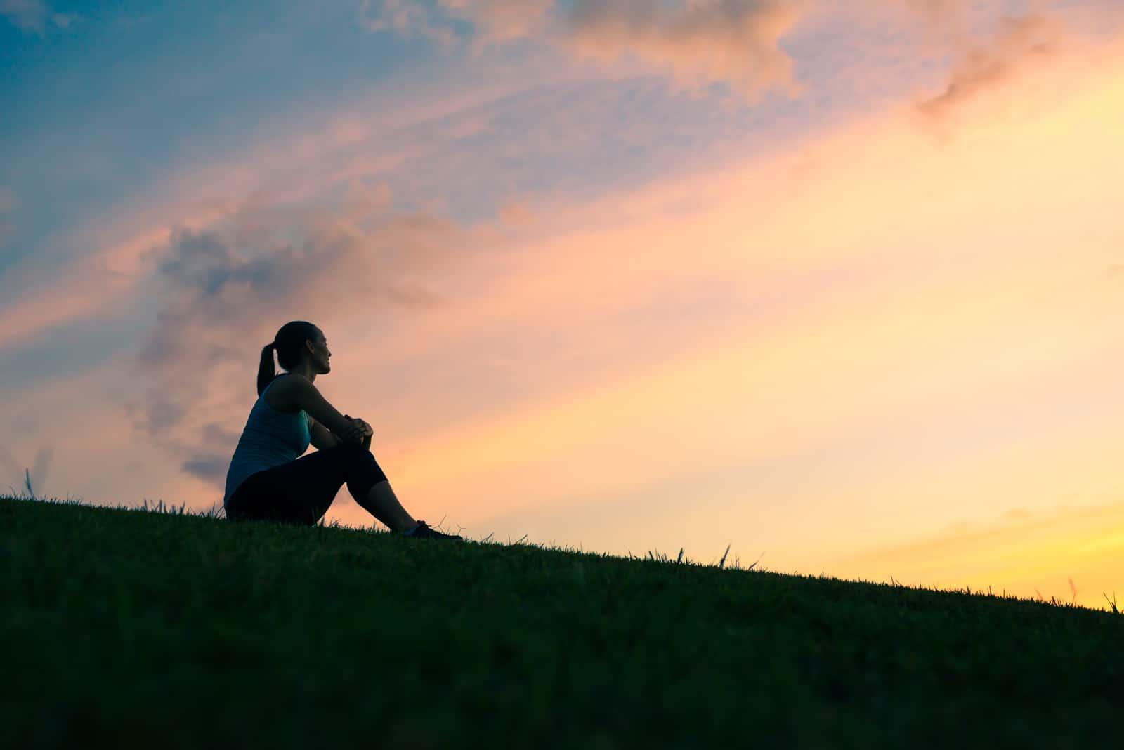 une femme assise dans un pré
