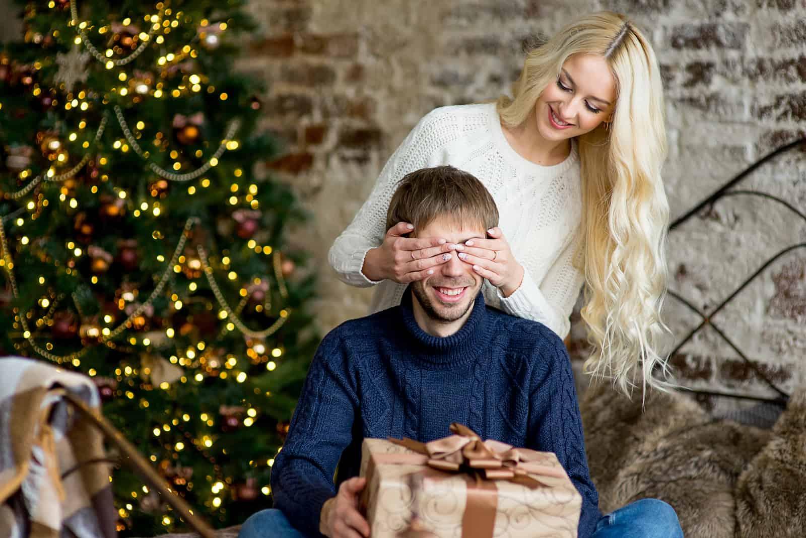une femme aux cheveux blonds a fermé les yeux de l'homme et lui a offert un cadeau