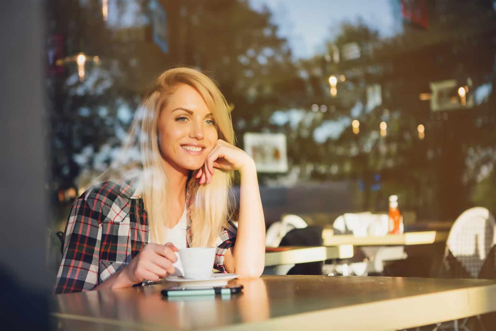 une femme aux cheveux blonds est assise et boit du café