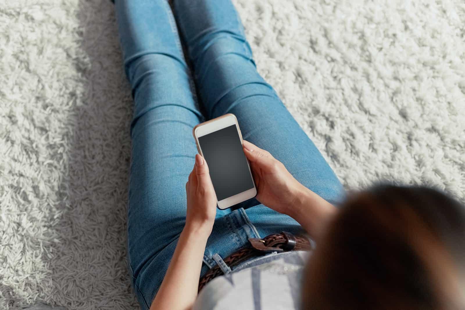 une femme aux cheveux bruns est assise sur le sol et un bouton du téléphone