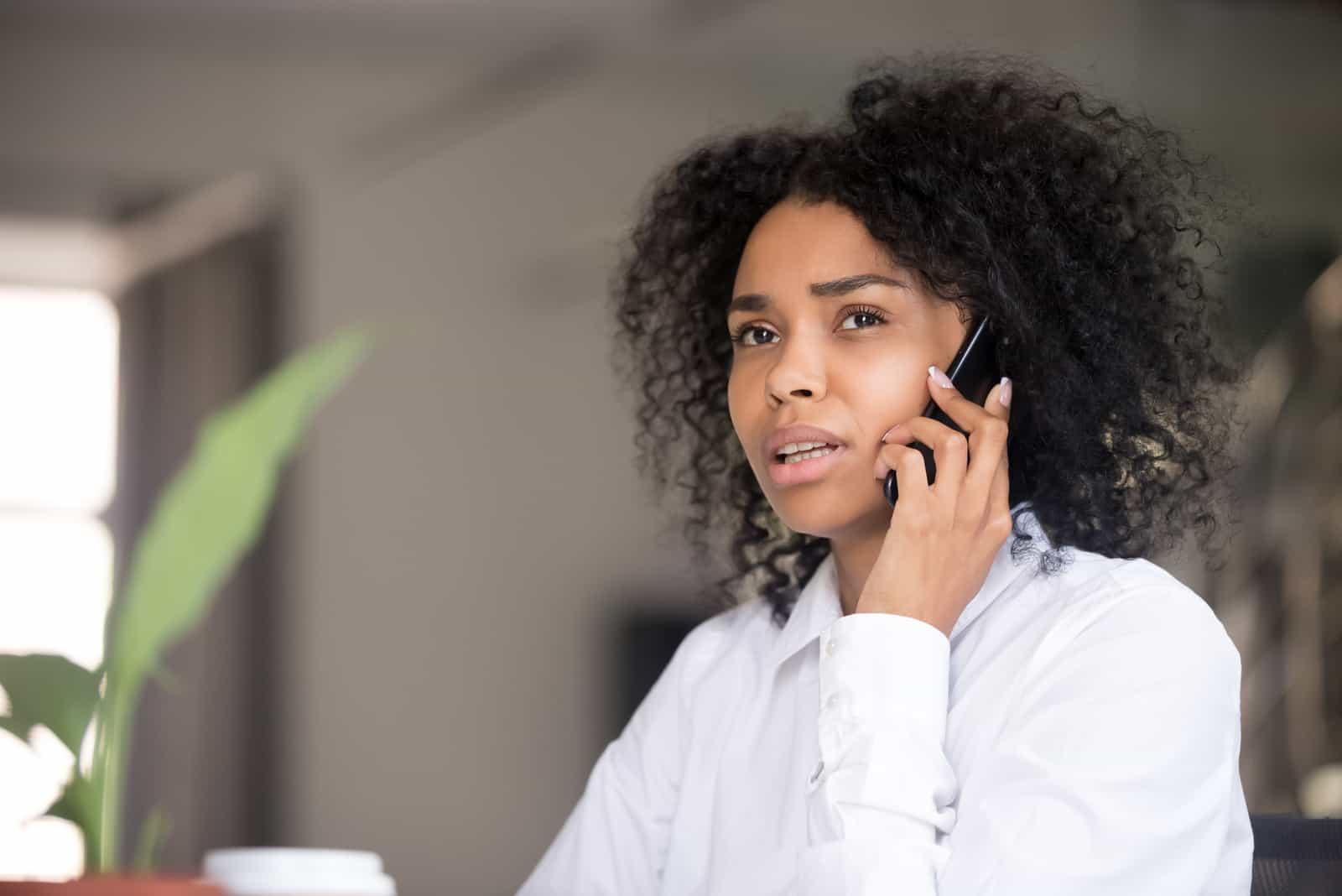 une femme aux cheveux crépus est assise et parle au téléphone