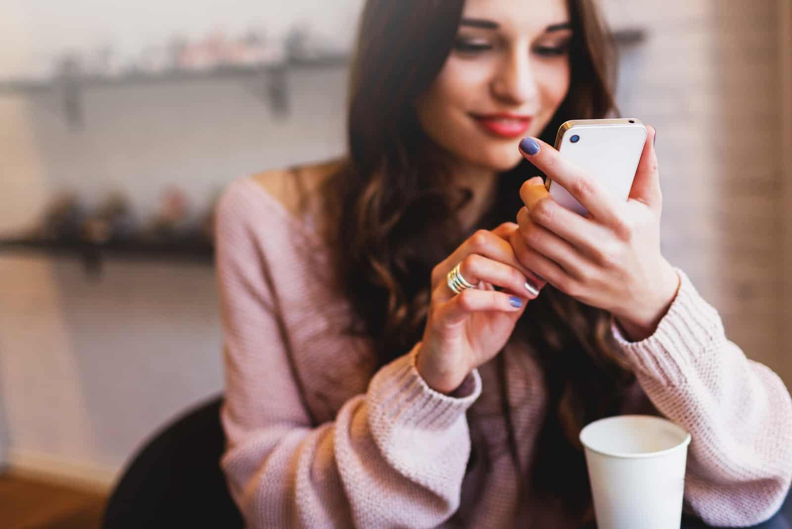 une femme aux longs cheveux bruns est assise en train de boire du café et d'appuyer sur un téléphone