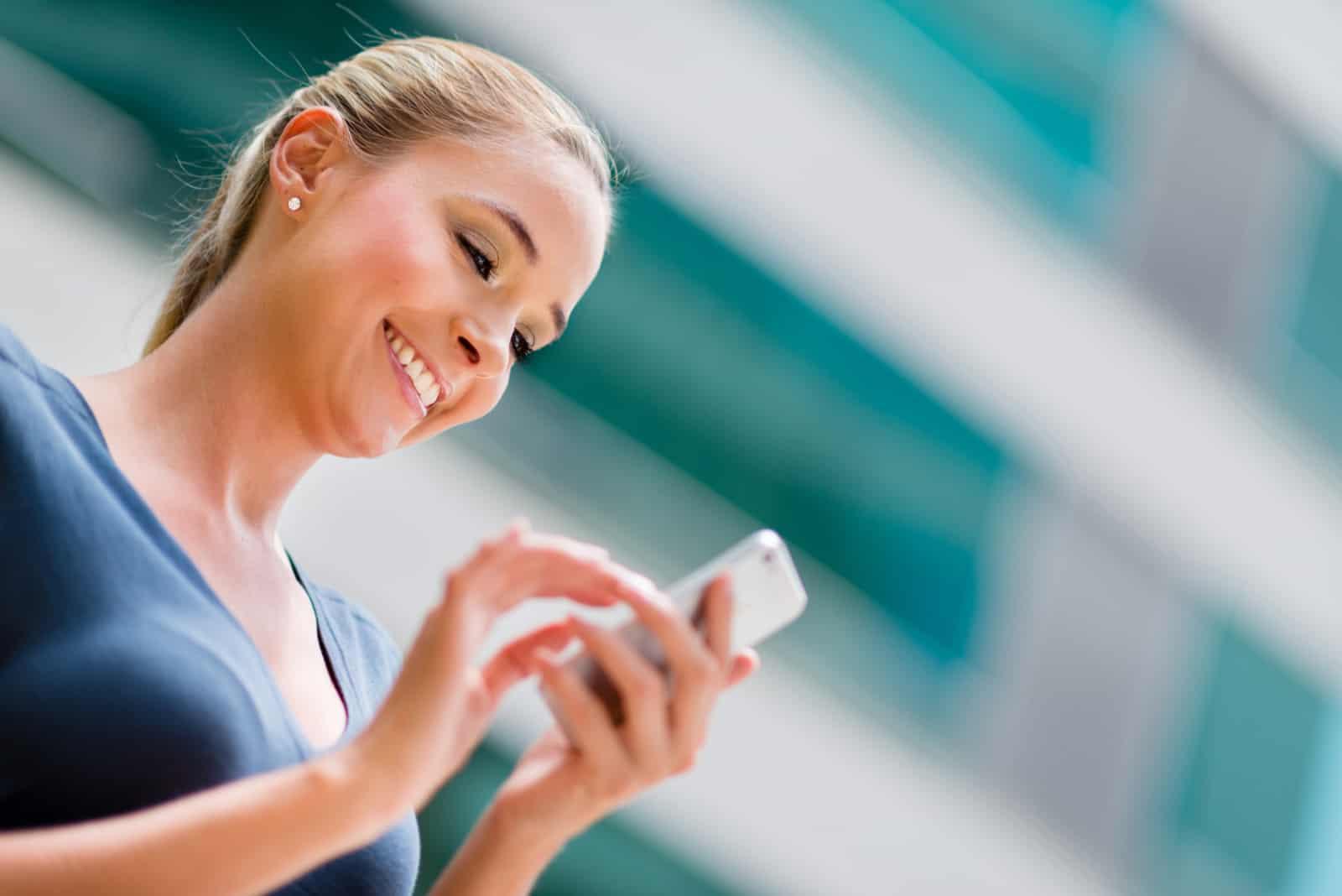 une femme blonde souriante se dresse et des boutons sur le téléphone