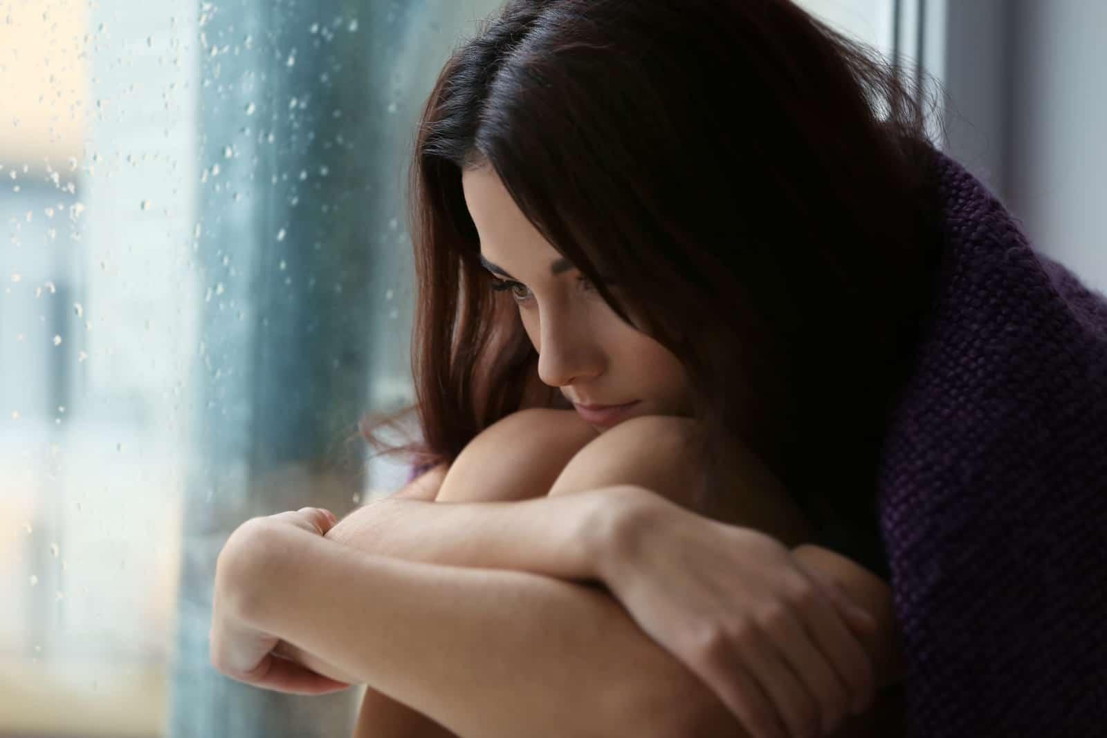 une femme déçue est assise près de la fenêtre