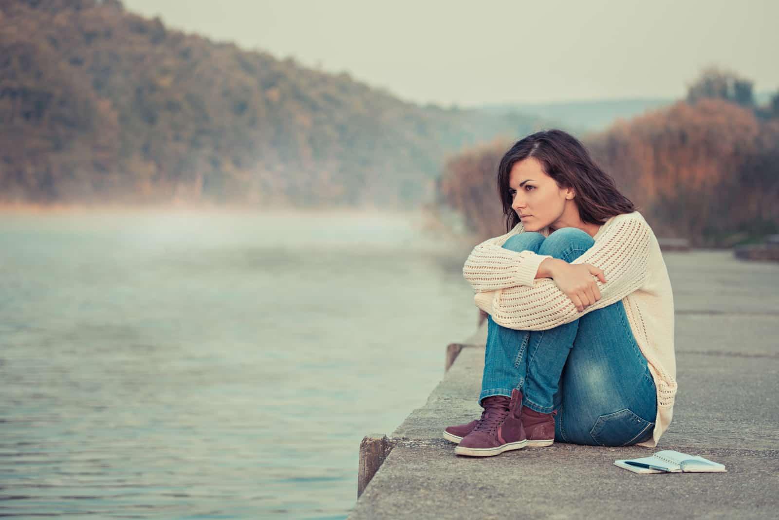 une femme déçue est assise sur une jetée