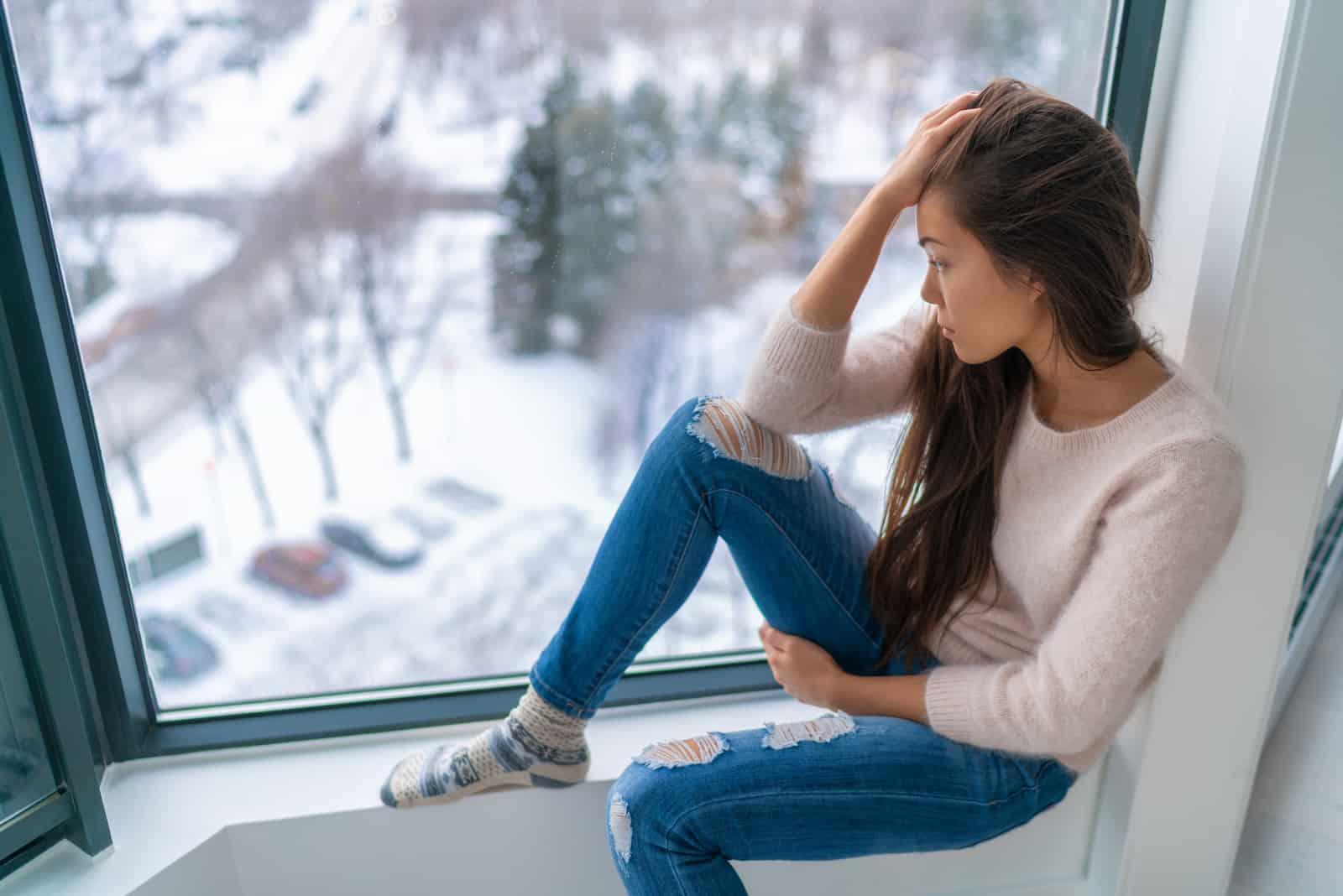 une femme déçue s'assoit et regarde par la fenêtre