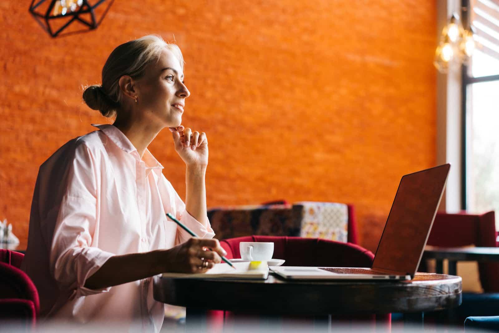une femme est assise à une table et écrit une chanson