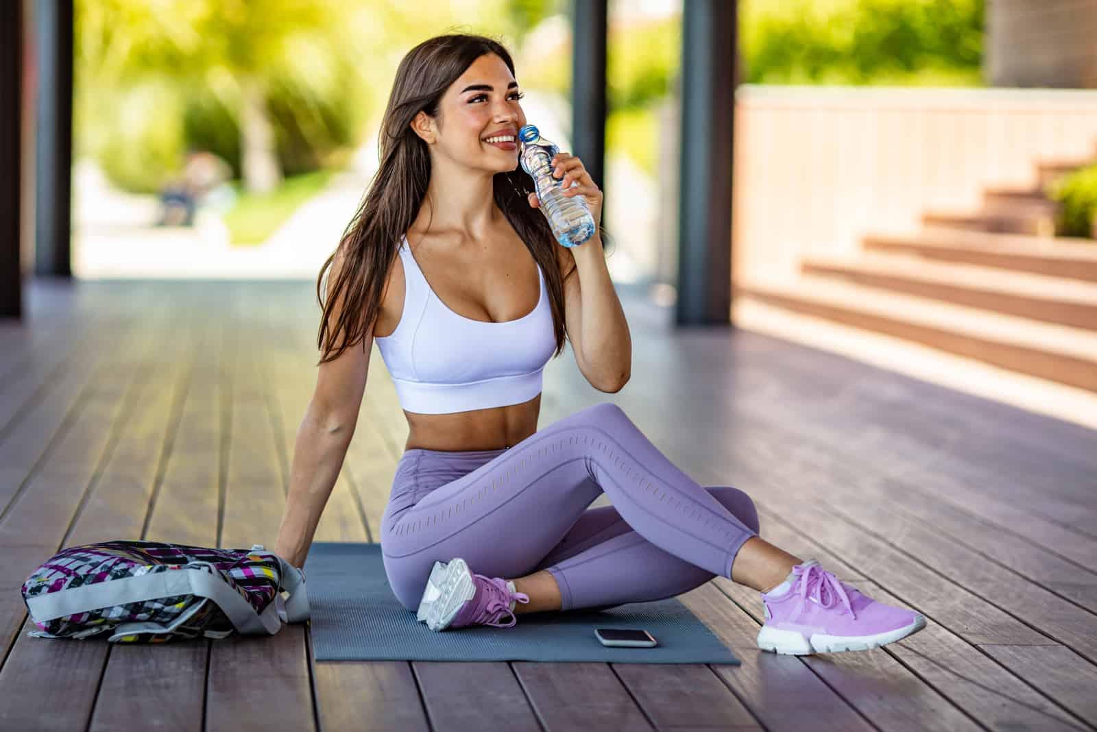 une femme est assise sur le sol en faisant de l'exercice et en buvant de l'eau