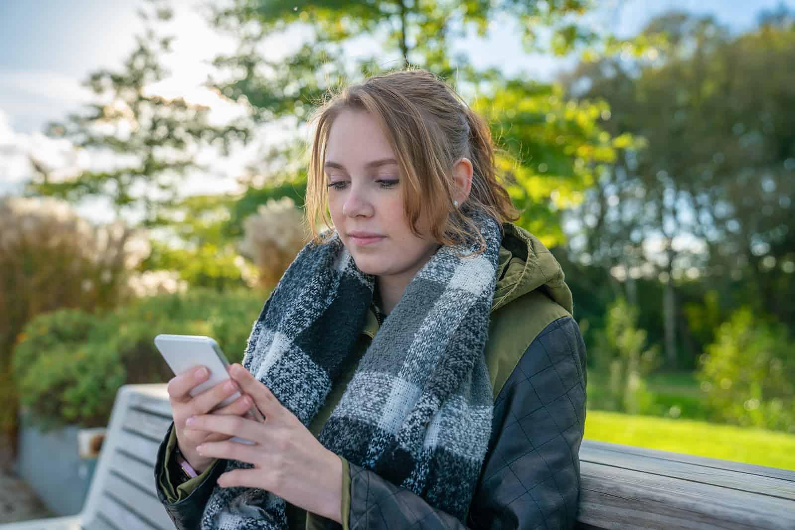 une femme est assise sur un banc de parc et écrit