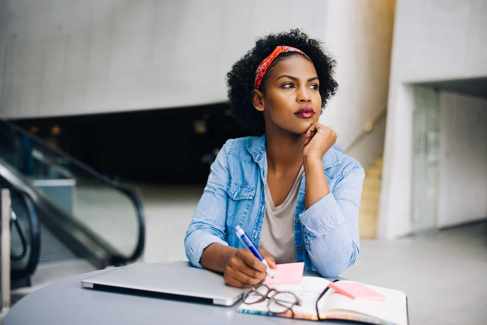 une femme imaginaire aux cheveux crépus est assise à une table et écrit