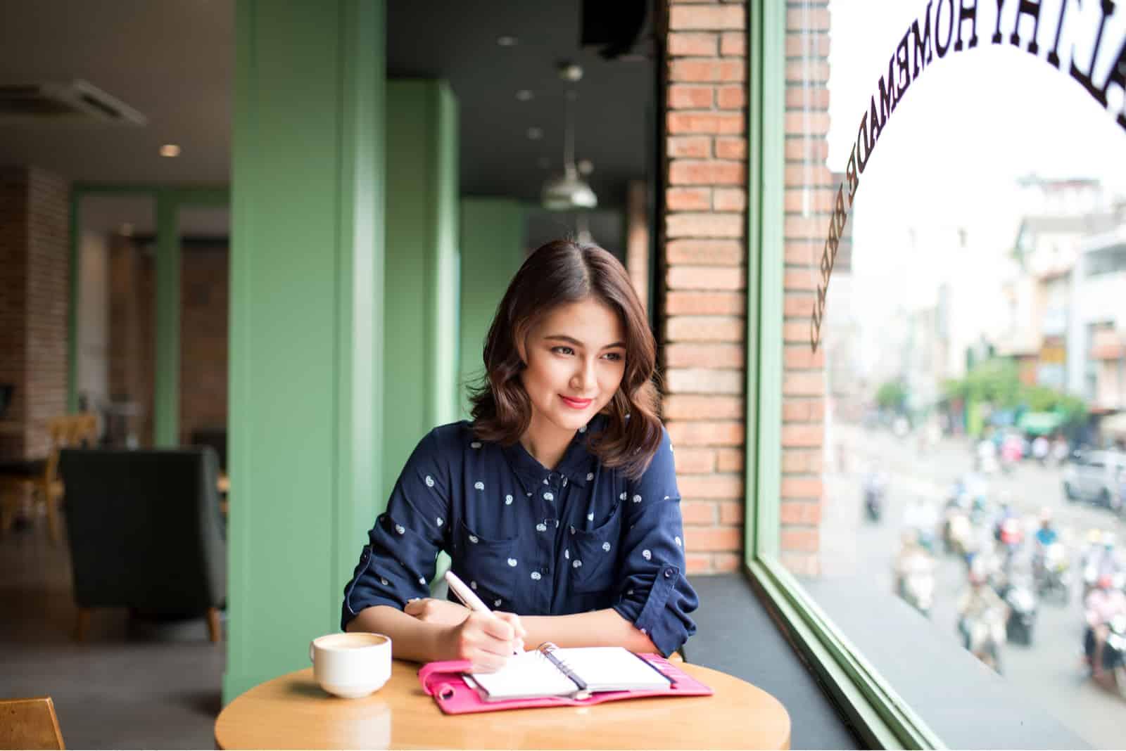 une femme imaginaire est assise à une table et écrit