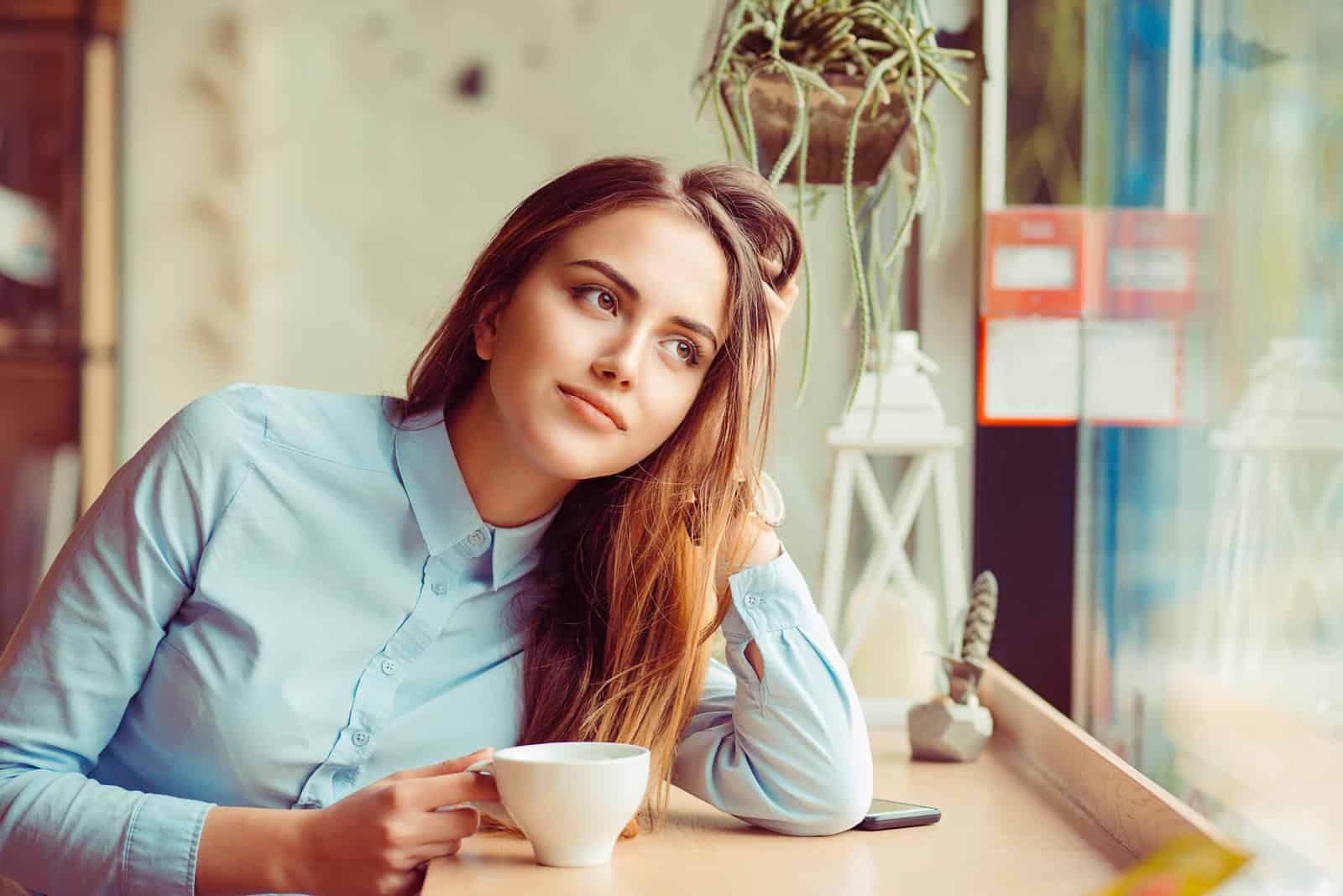 une femme imaginaire est assise et boit du café