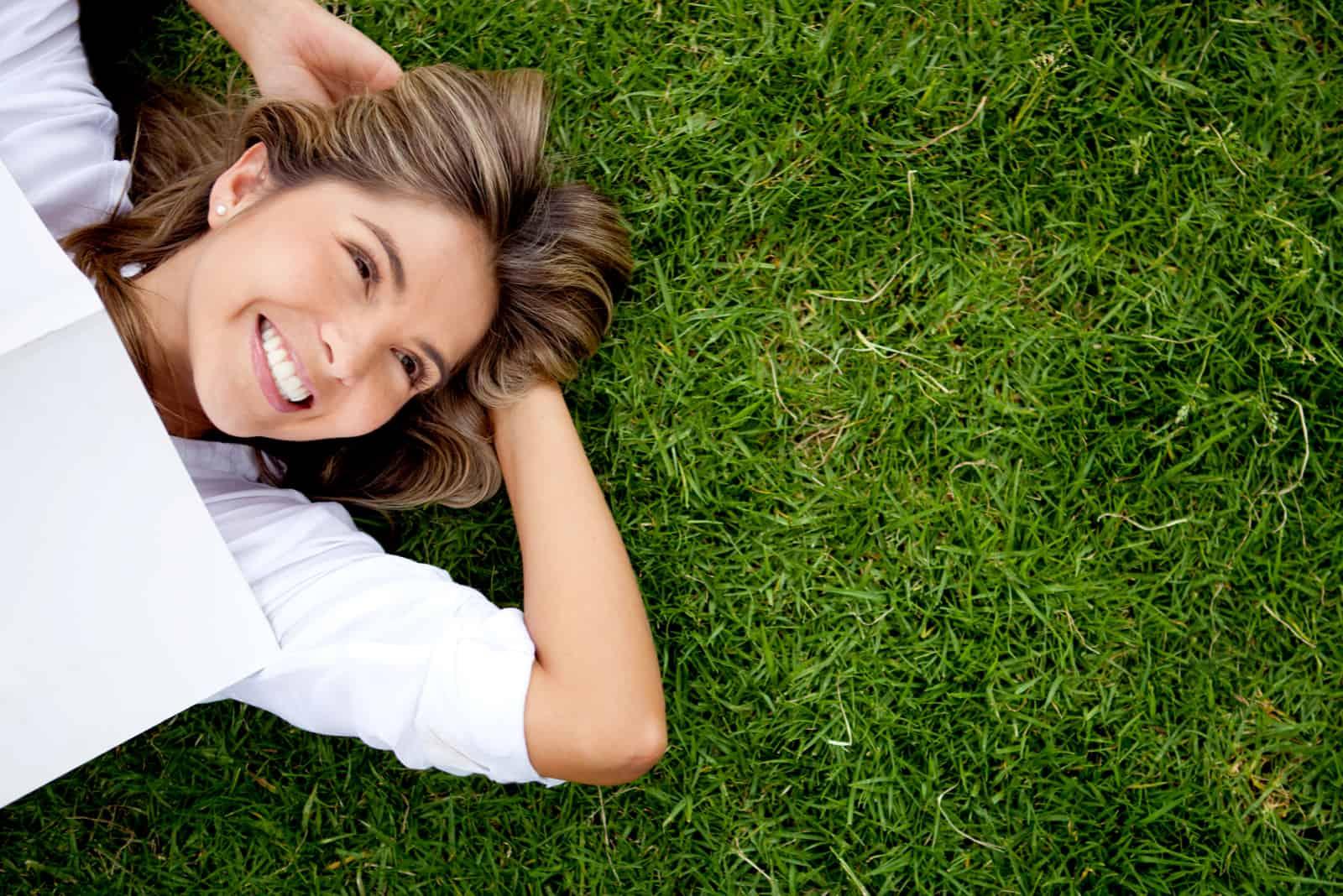 une femme souriante allongée sur l'herbe