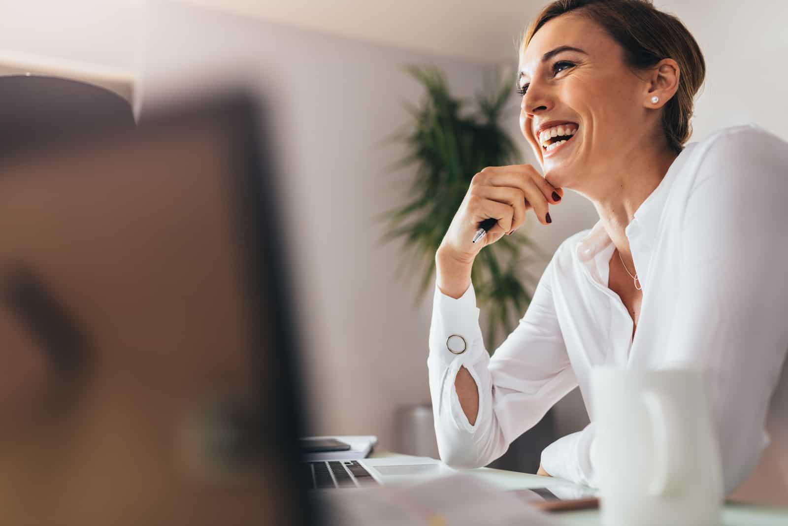 une femme souriante assise au travail