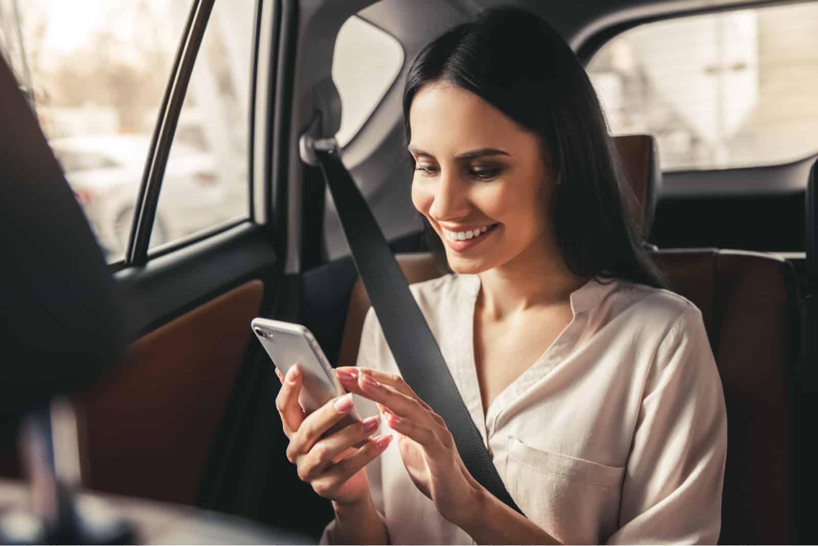 une femme souriante assise dans la voiture et tapant au téléphone