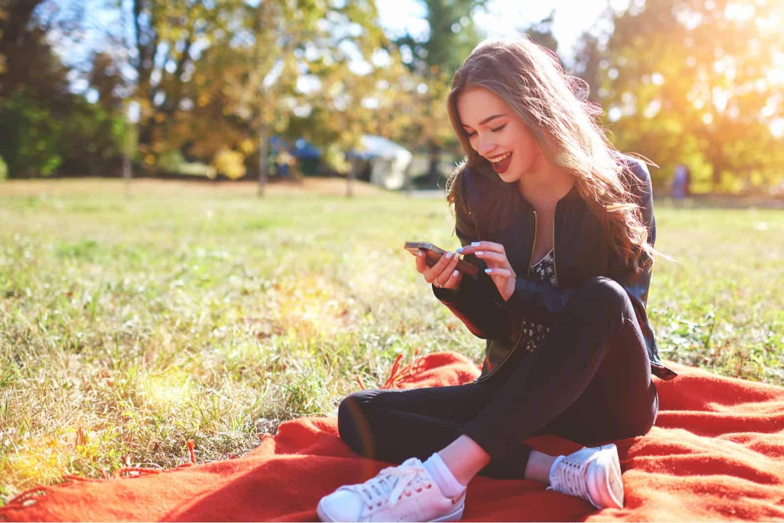 une femme souriante assise sur une couverture dans le parc et tapant au téléphone
