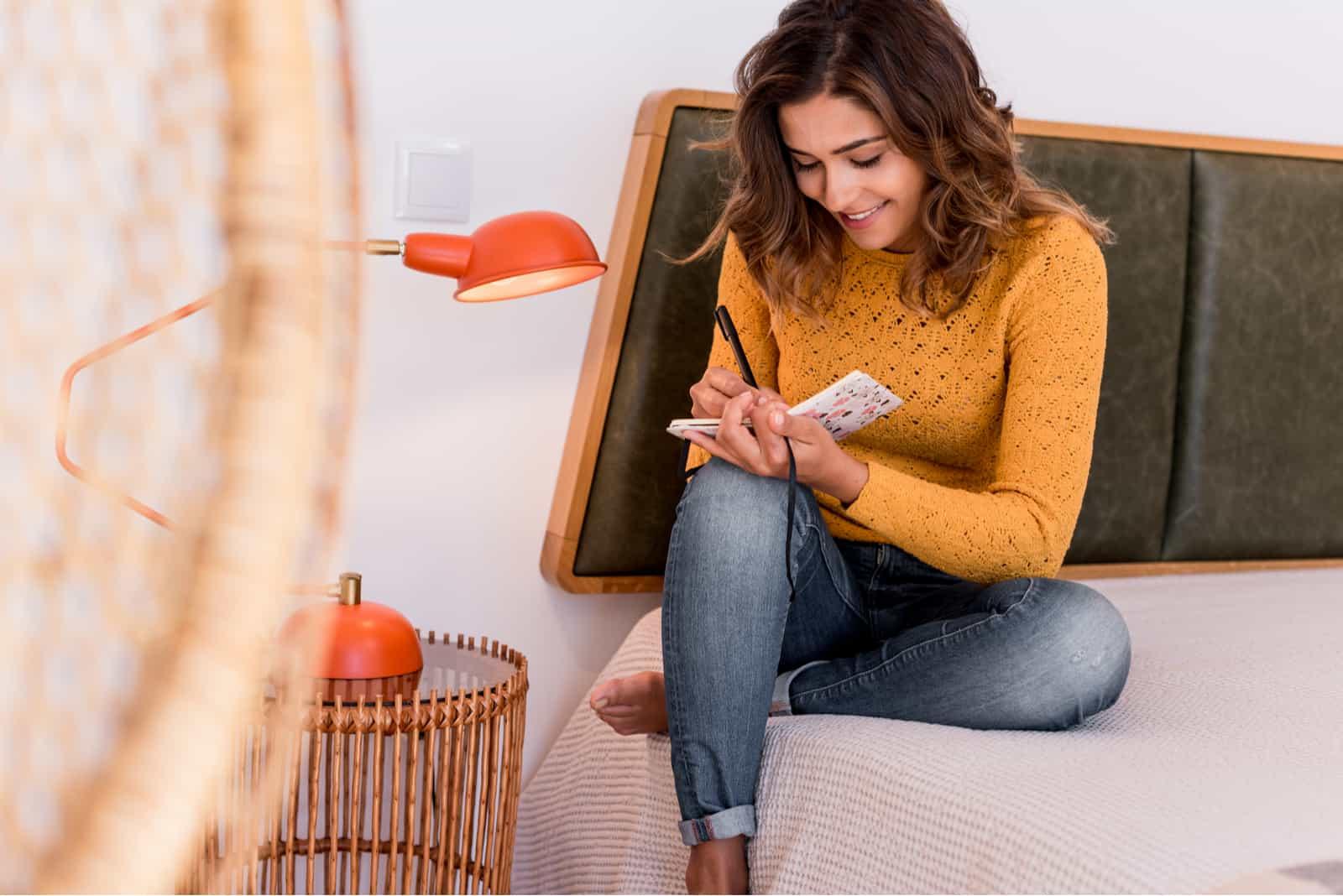 une femme souriante aux cheveux crépus est assise sur le lit et écrit