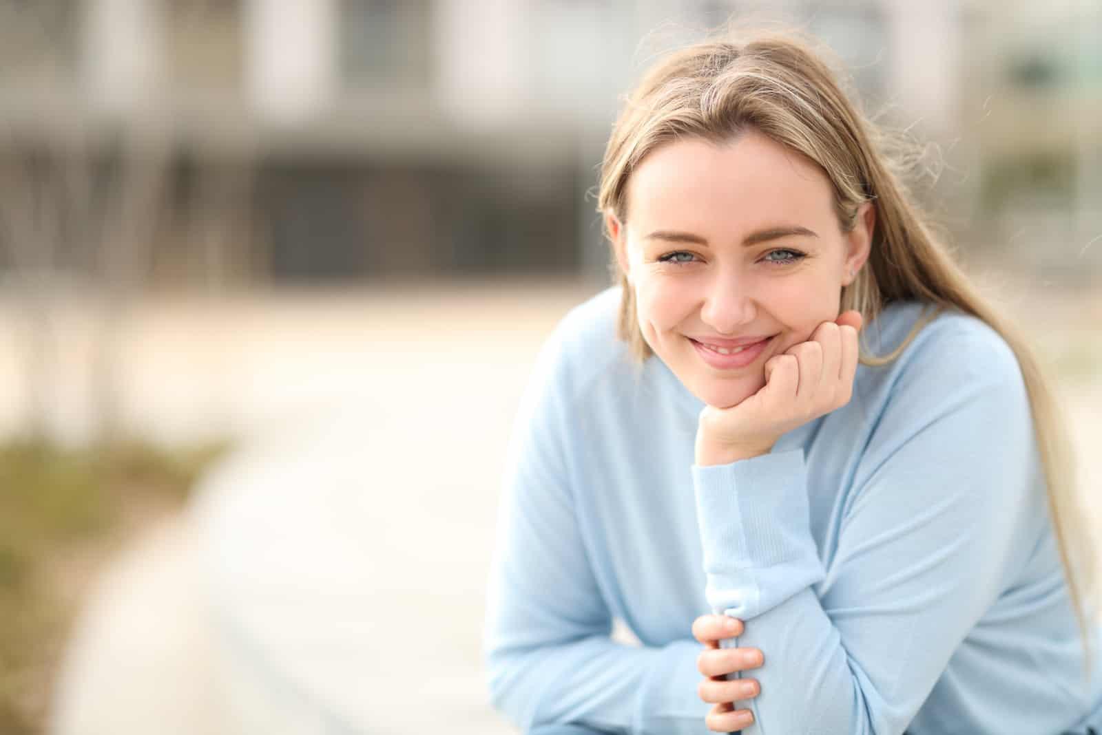 une femme souriante aux longs cheveux blonds