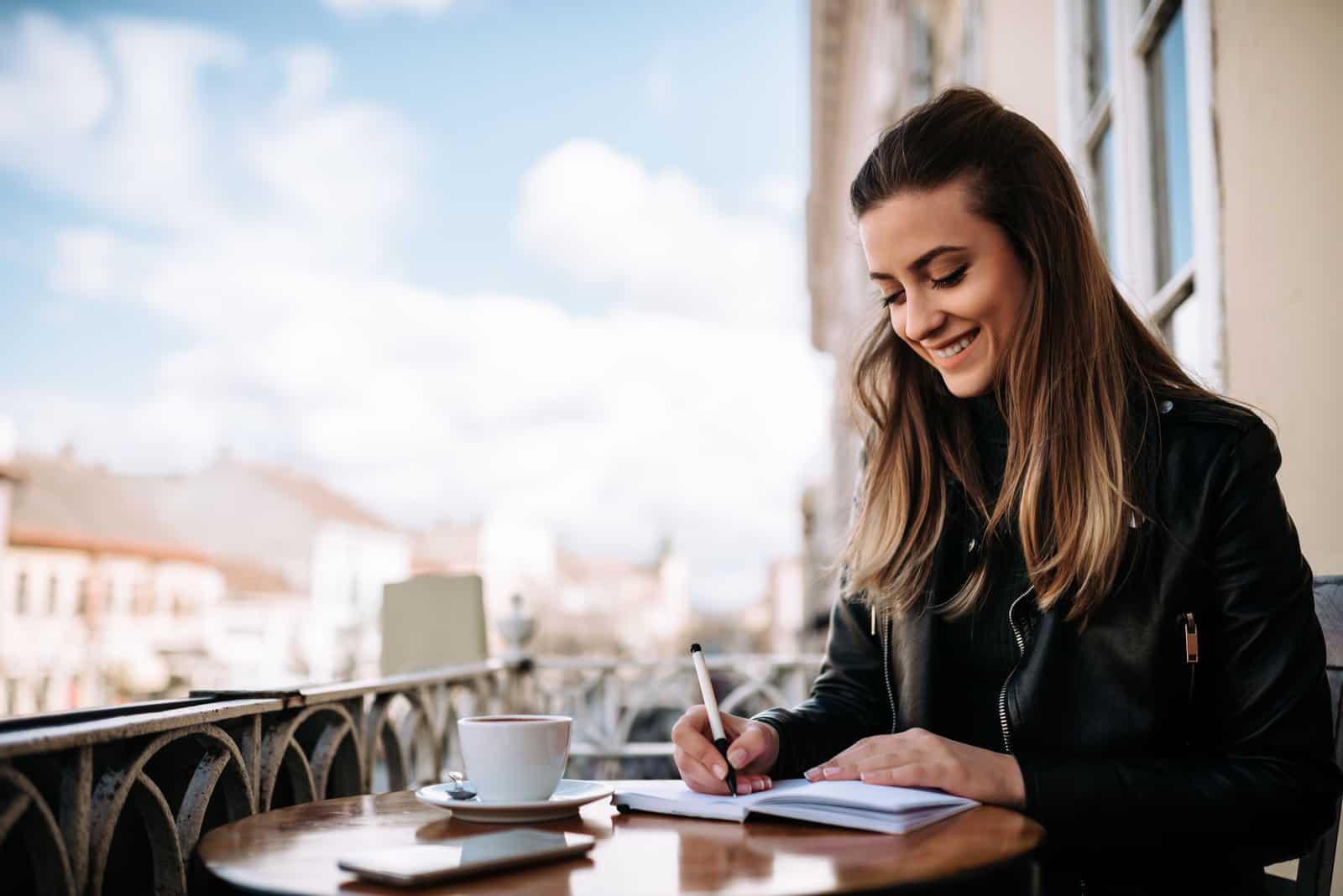 une femme souriante avec du café est assise à une table et écrit