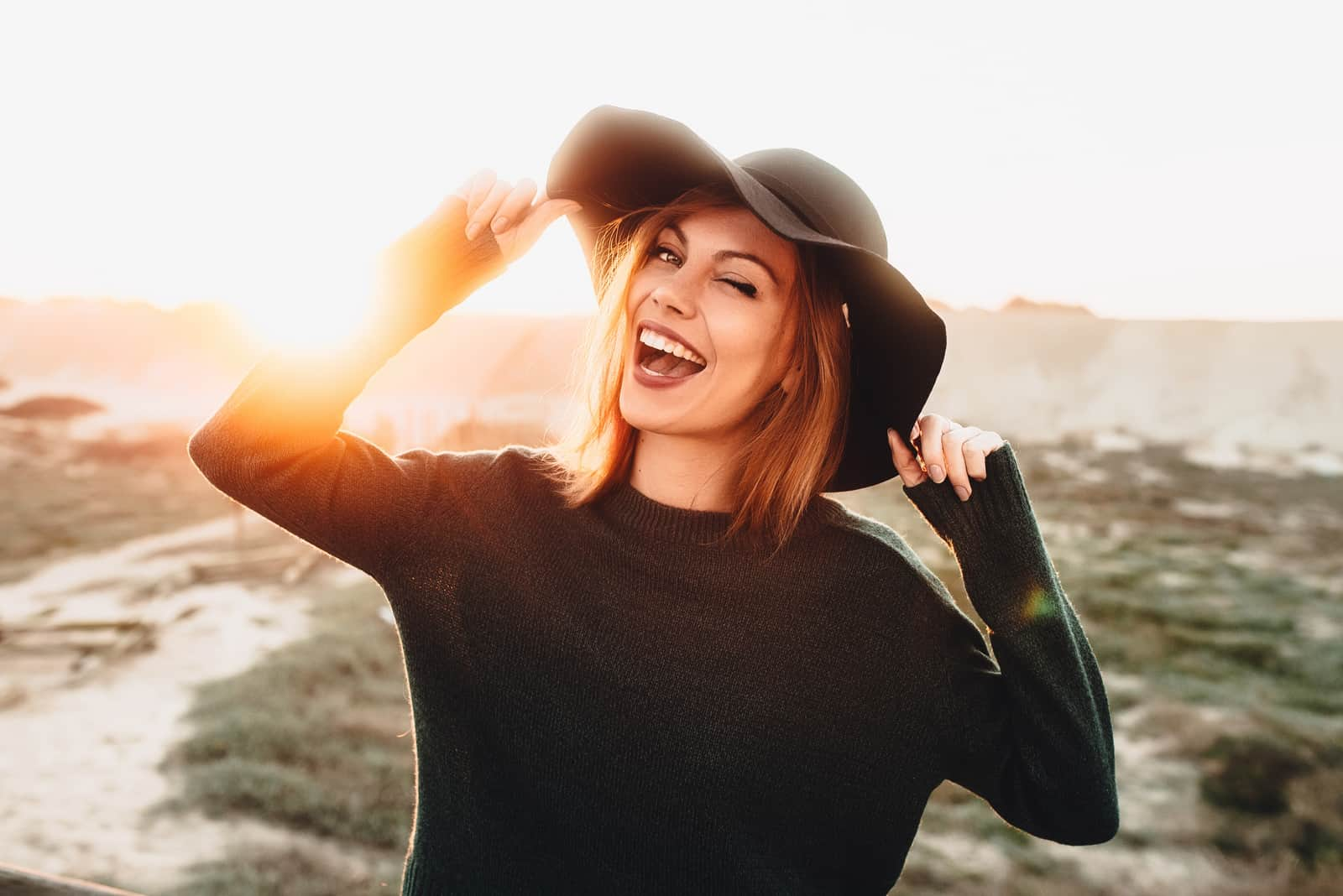 une femme souriante avec un chapeau noir sur la tête