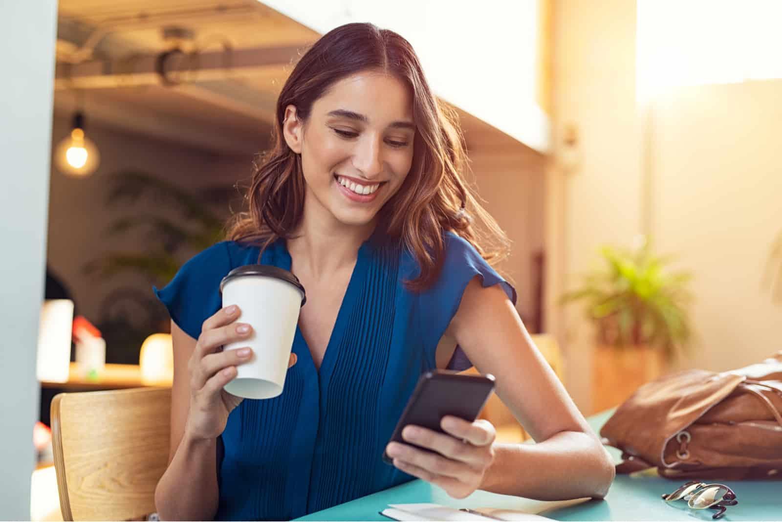 une femme souriante est assise à une table et tient un téléphone à la main