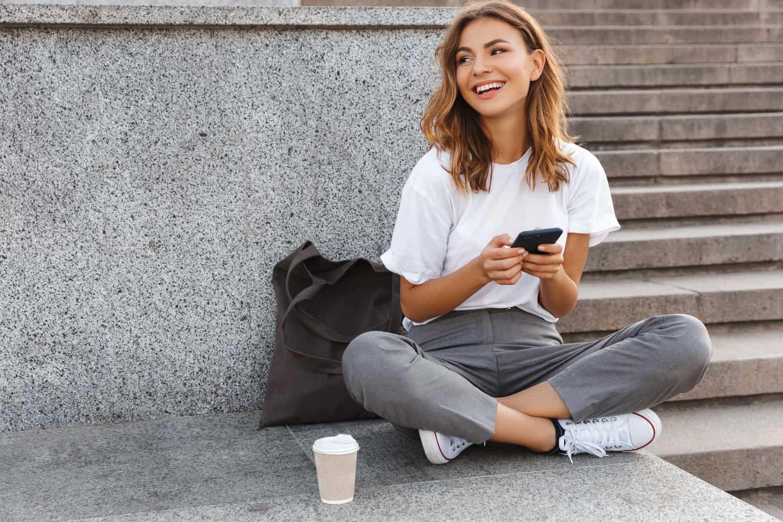 une femme souriante est assise sur le dos et les boutons du téléphone