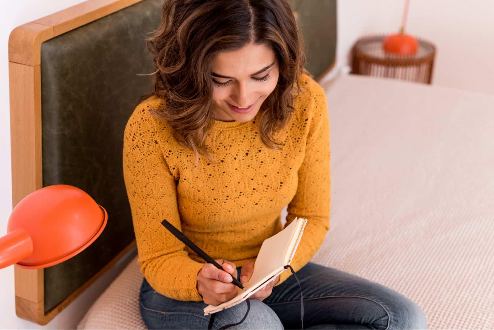 une femme souriante est assise sur le lit et écrit