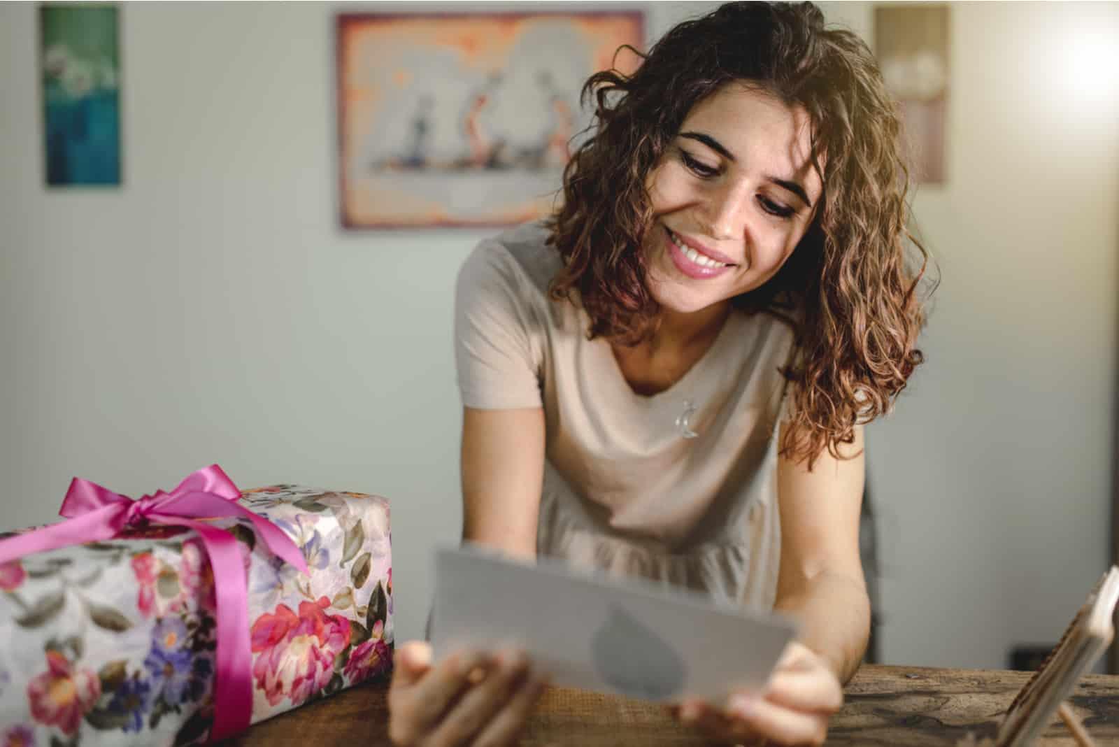 une femme souriante lit une carte de voeux