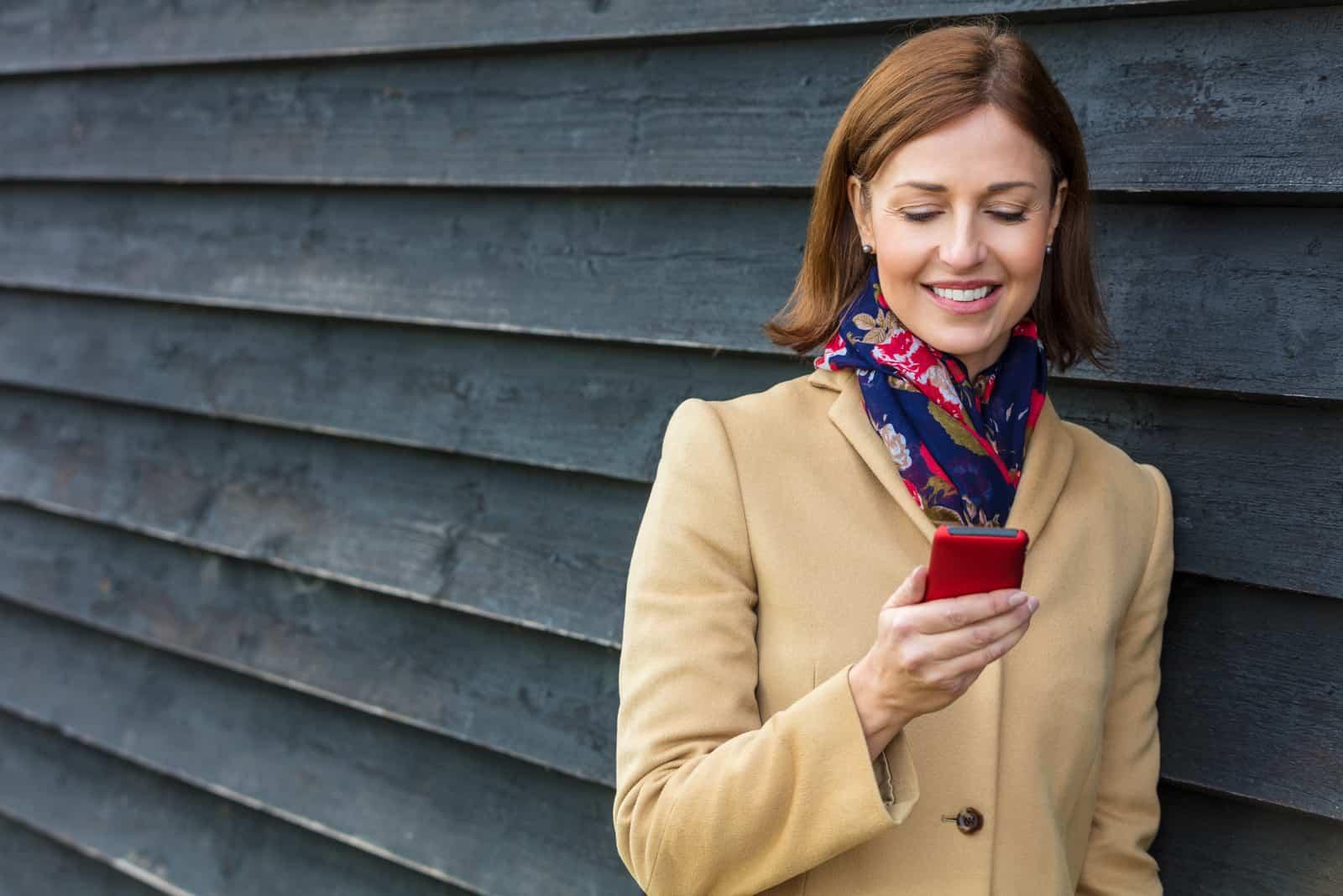 une femme souriante se lève et un bouton sur le téléphone