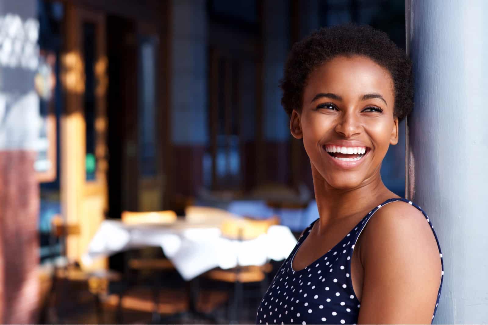 une femme souriante se tient appuyée contre un mur