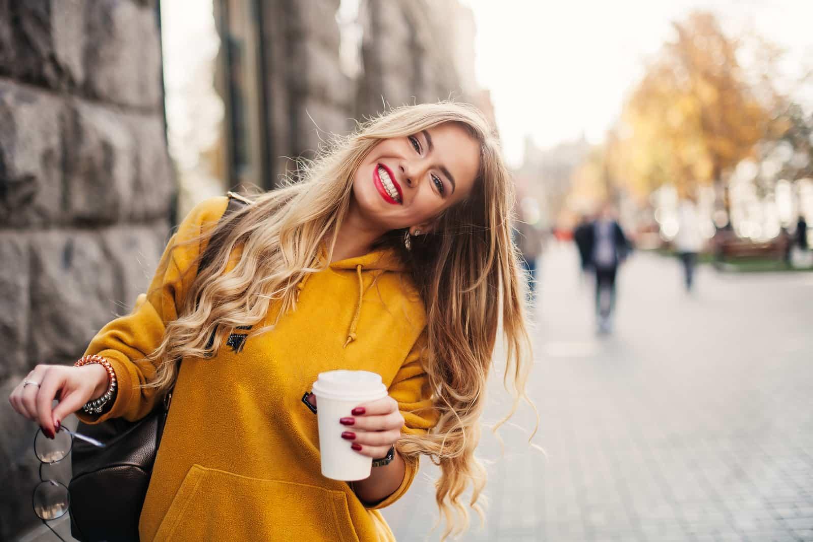 une femme souriante se tient dans la rue tenant un café à la main