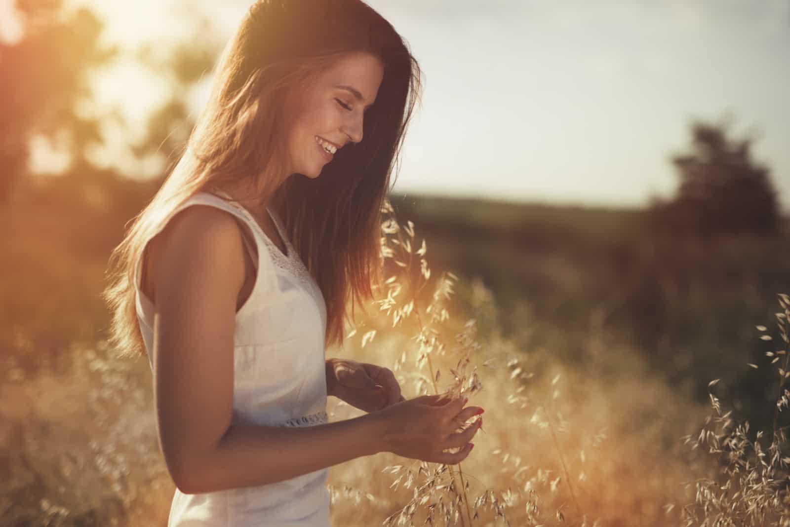 une femme souriante se tient dans un champ
