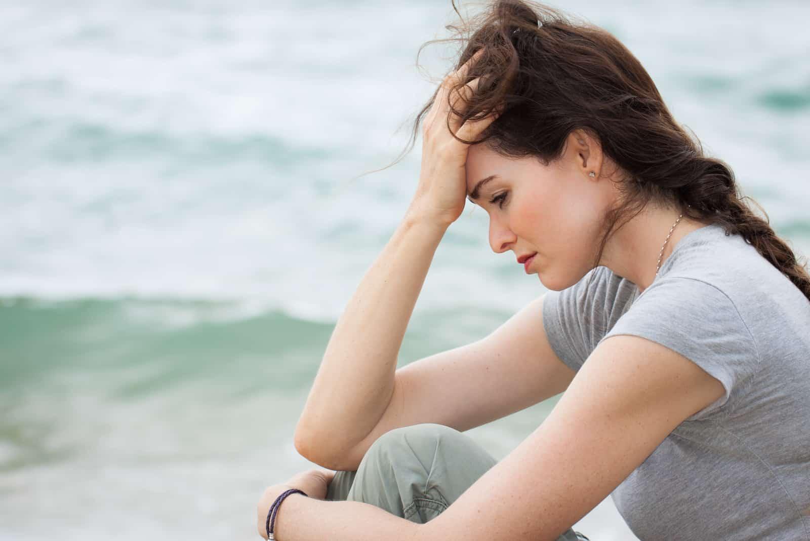 une femme triste assise au bord de la mer