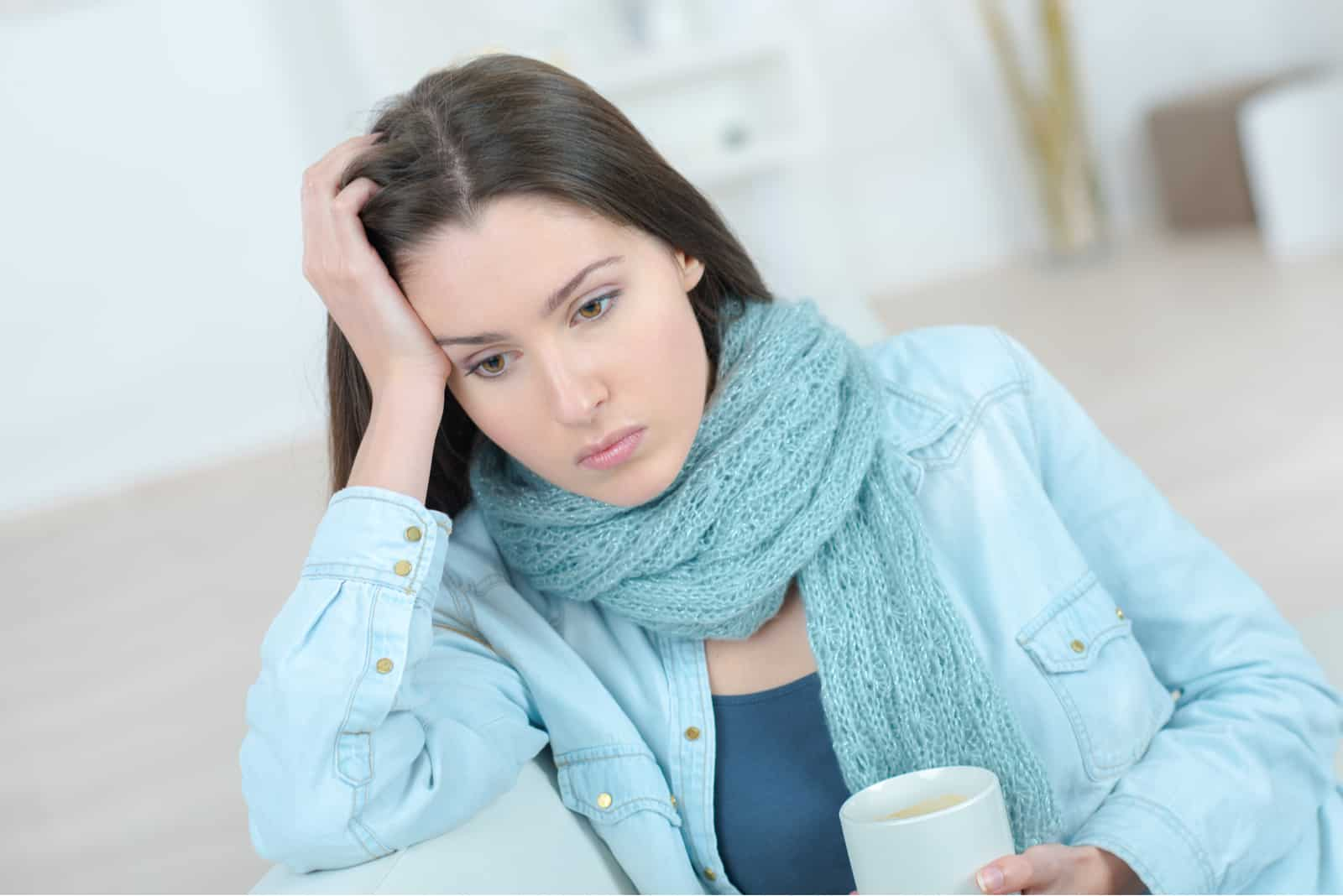 une femme triste est assise sur le canapé et boit du café