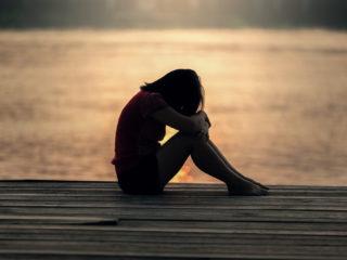 femme triste assise sur un quai près de la mer