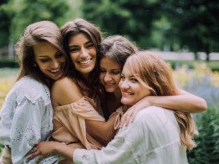 quatre femmes s'embrassant en plein air