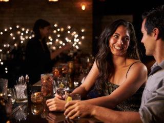 homme et femme parlant assis dans un bar