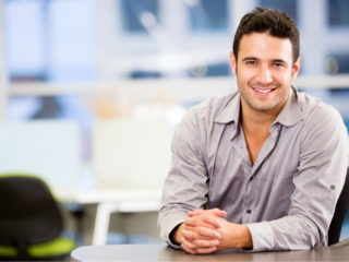 un homme souriant assis à une table