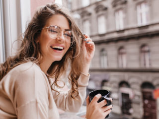 une femme souriante avec des lunettes boit du café