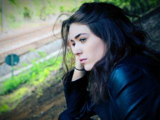 femme triste en veste noire assise sur le sol
