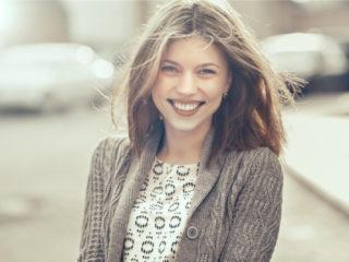 une belle femme aux longs cheveux bruns se tient dans la rue et rit